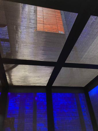 Looking up through the transparent elevator cab to the glowing, blacklight painted shaft.